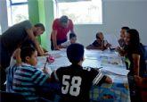 Los participantes en el proyecto 'integración socioeducativa de menores y jóvenes  en situación o riesgo de exclusión social' realizan un taller de informática