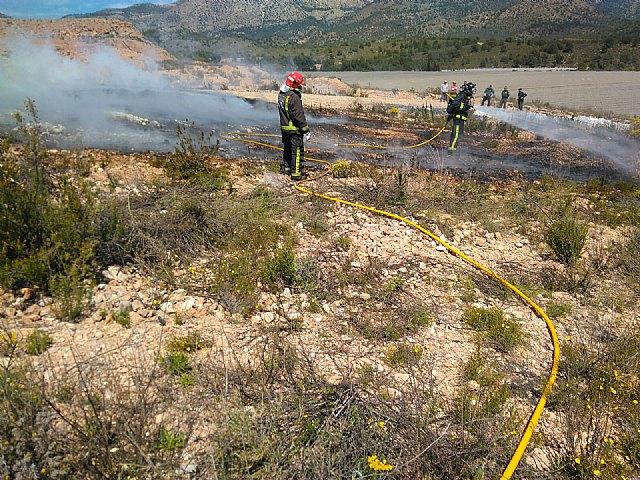 Bomberos del CEIS y agente medioambiental apagan una quema de plásticos junto al monte, en Aledo, Foto 2