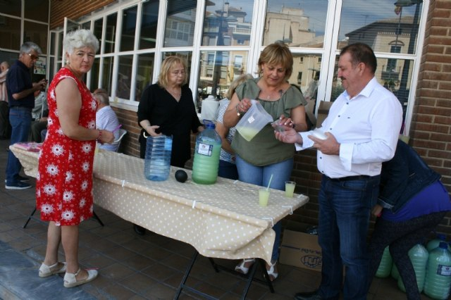Partners and users of the Municipal Center for the Elderly of the Balsa Vieja square enjoy the distribution of lemon water on the occasion of the festivities