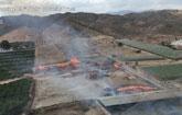 Helicóptero de la DGSCyE y bomberos del Consorcio trabajan en la extinción del incendio en una granja en Totana