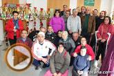 Usuarios de los centros de día para la discapacidad hacen entrega a la Asociación de Comerciantes de los adornos de Navidad que decorarán de forma uniforme los establecimientos adheridos a esta entidad
