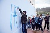 Los jóvenes, inscritos en el 'Taller de Grafiti', ya han empezado a pintar el que será el gran grafiti del Pabellón de Deportes de La Cañadica