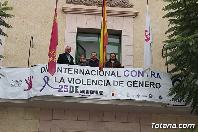 They place the commemorative banner for the International Day against Gender Violence on the façade of the Town Hall