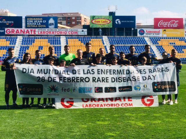 Jugadores del UCAM Murcia CF posaron con una pancarta del Día Mundial de las ER para dar visibilidad a las patologías poco frecuentes
