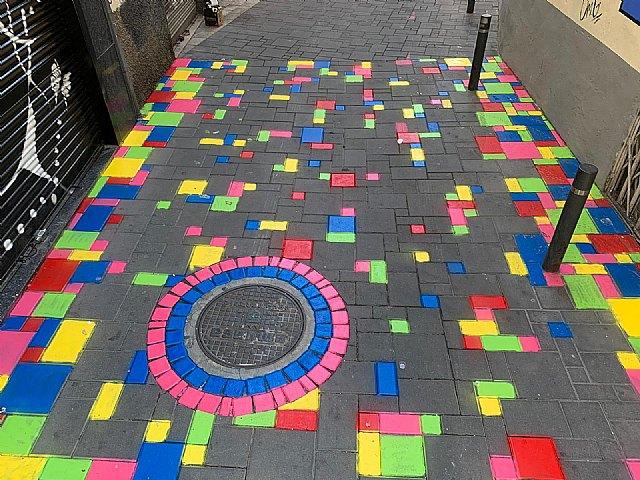 La calle Angustias estrena una alfombra multicolor en sus