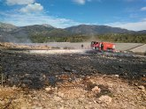 Bomberos del CEIS y agente medioambiental apagan una quema de plásticos junto al monte, en Aledo