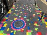 La calle Angustias estrena una alfombra multicolor en sus adoquines