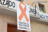 Totana conmemora hoy el Día Mundial de los Animales abogando por políticas contra el maltrato, con la colocación de un cartel con lazo naranja en la fachada consistorial