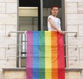 Mª Carmen Morales cuelga la bandera arcoirís para celebrar el Día Internacional del Orgullo